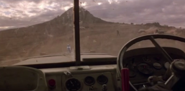 A truck driver's POV on a barren desert mountain.